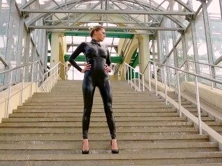 Fit Blonde Babe Walking In Latex Catsuit