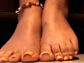 She Shows Off Her Pretty Orange Painted Toes